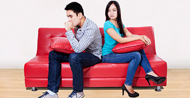 couple on couch angry with each other.