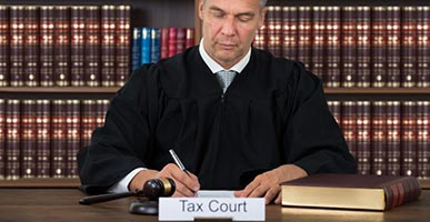 Tax Court judge signing documents at a desk
