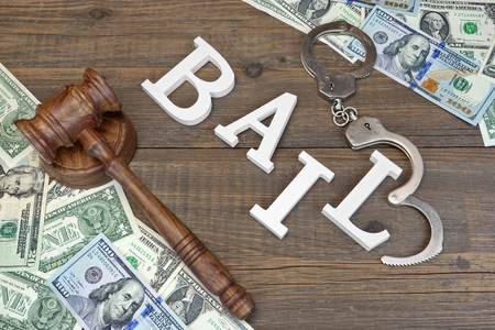 Image of money and handcuffs and gavel with word bail