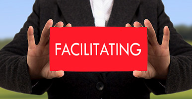 Person holding card that says Facilitating