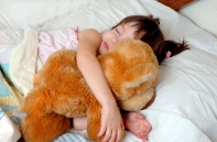 Image of child sleeping with a teddy bear