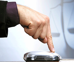 Person clicking a mouse button; scales of justice in background
