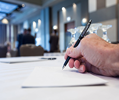 Hand writing on paper at a conference